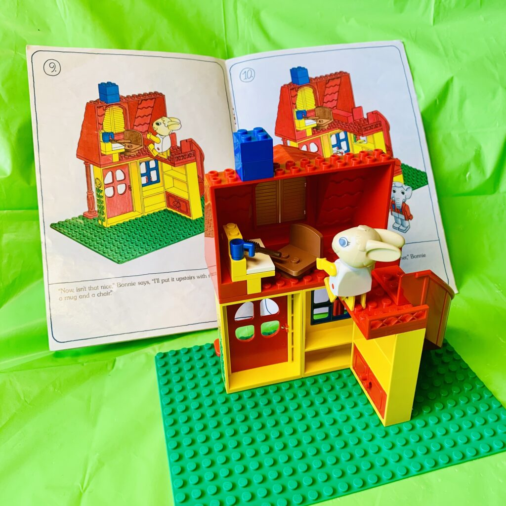 Instruction manual showing how to build the upstairs, with LEGO model in foreground.