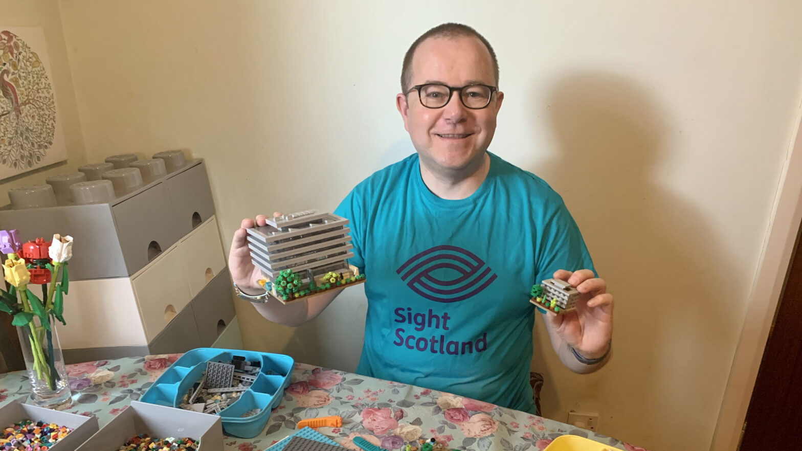 Stewart wearing his 'Sight Scotland' teal coloured t-shirt, holding up both his Main Library Lego models.